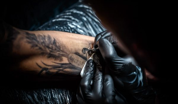 Close up image of the tattoo artist makes a tattoo on a man arm.