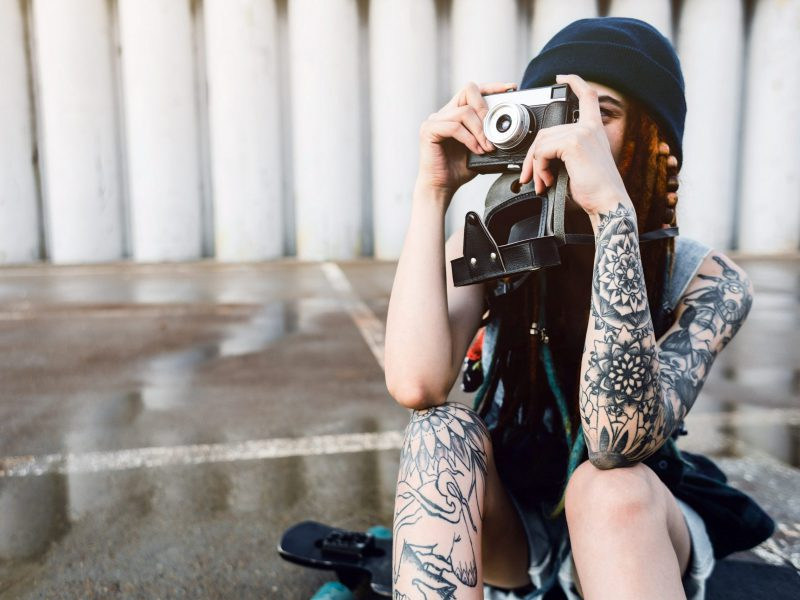young girl with tattoos and dreadlocks in a blue hat photographs a vintage camera on the background of a concrete wall.
