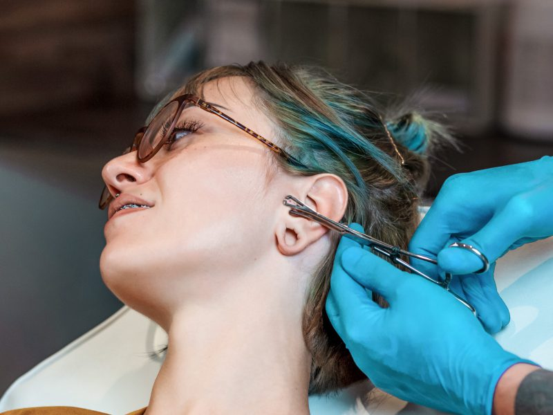 Young Woman getting her ear pierced. Man showing a process of piercing with steril medical equipment and latex gloves. Body Piercing Procedure